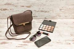 Małe brown damy torebka, okulary przeciwsłoneczni, mądrze telefon, eyeshadow paleta i pomadka na drewnianym tle, piękna błękitny  fotografia royalty free
