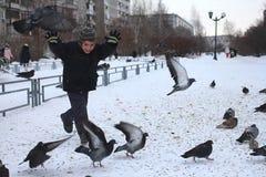 Małe chłopiec przejażdżki w parku ptaków gołębie w zimie śmiają się zabaw emocje zdjęcie stock