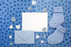 Małe chłopiec skarpety, pusta karta i evelop na błękitnym drewnianym tle, Mieszkanie nieatutowy Zdjęcia Royalty Free