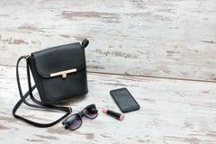 Małe czarne damy torebka, okulary przeciwsłoneczni, pomadka i mądrze phon, zdjęcie royalty free