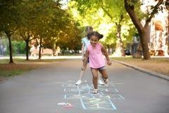 Małe dzieci bawić się hopscotch rysującego z kolorową kredą obraz stock