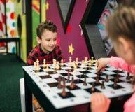 Małe dzieci bawić się szachy w rozrywki centrum obrazy stock