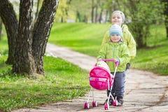 Małe dzieci bawić się w jardzie z dziecka ` s zabawki lalą dla lal chłopiec i dziewczyna bawić się grę dzieci bawić się spacerowi Obraz Stock