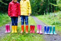 Małe dzieci, chłopiec i dziewczyny w kolorowych podeszczowych butach, Dzieci stoi w jesieni lasowym zakończeniu schoolkids i zdjęcie royalty free