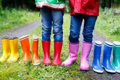 Małe dzieci, chłopiec i dziewczyny w kolorowych podeszczowych butach, Dzieci stoi w jesieni lasowym zakończeniu schoolkids i obrazy royalty free