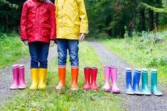 Małe dzieci, chłopiec i dziewczyny w kolorowych podeszczowych butach, Dzieci stoi w jesieni lasowym zakończeniu schoolkids i zdjęcie stock