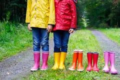 Małe dzieci, chłopiec i dziewczyny w kolorowych podeszczowych butach, Dzieci stoi w jesieni lasowym zakończeniu schoolkids i obraz stock