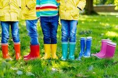 Małe dzieci, chłopiec lub dziewczyny w, cajgach i żółtej kurtce w kolorowych podeszczowych butach obraz stock