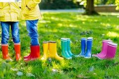 Małe dzieci, chłopiec lub dziewczyny w, cajgach i żółtej kurtce w kolorowych podeszczowych butach obraz royalty free