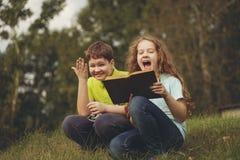 Małe dzieci czyta książkę outdoors jest edukacja starego odizolowane pojęcia obrazy stock