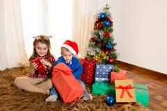 Małe dzieci na dywaniku otwiera Bożenarodzeniowe teraźniejszość Obraz Royalty Free