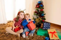 Małe dzieci na dywaniku otwiera Bożenarodzeniowe teraźniejszość Fotografia Royalty Free