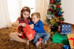 Małe dzieci na dywaniku otwiera Bożenarodzeniowe teraźniejszość Obrazy Stock