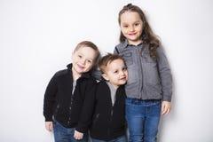 Małe dzieci stoi wpólnie odizolowywający na szarym tle obrazy stock