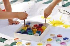 Małe dziecka ` s ręki malują z farbami i muśnięcia na ampule ciąć na arkusze na ulicie na słonecznym dniu, twórczości i zabawie, obrazy royalty free
