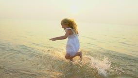 Małe dziecko, śliczny dziewczyny dziewczyny bieg na plaży podczas pięknego zmierzchu szczęśliwego urlopowego czasu w zwolnionym t zdjęcie wideo