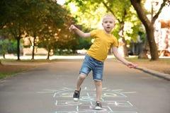 Małe dziecko bawić się hopscotch rysującego z kolorową kredą zdjęcia royalty free