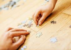 Małe dziecko bawić się z łamigłówkami na drewnianej podłoga wraz z rodzicem, stylu życia pojęcia ludzie, kocha ręki each Zdjęcie Stock
