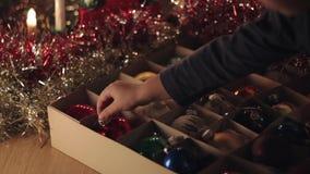 Małe dziecko bierze out roczników bożych narodzeń sfery zabawkę z pudełka zdjęcie wideo