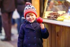 Małe dziecko chłopiec łasowania słodki jabłko na bożych narodzeniach wprowadzać na rynek obrazy royalty free