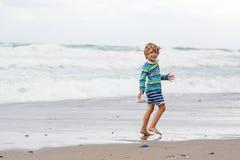 Małe dziecko chłopiec bawić się na plaży na burzowym dniu Fotografia Stock