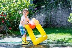 Małe dziecko chłopiec bawić się z ogrodowym wężem elastycznym obrazy royalty free