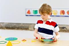 Małe dziecko chłopiec bawić się z udziałami kolorowy klingeryt blokuje zestaw w szkolnej lub preschool pepinierze dziecka zabawy  zdjęcia royalty free