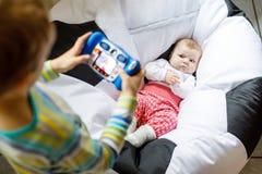 Małe dziecko chłopiec bierze obrazek z zabawkarską kamerą śliczna dziewczynka Fotografia Royalty Free