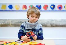 Małe dziecko chłopiec buduje geometryczne postacie z plastikowymi blokami Zdjęcia Stock