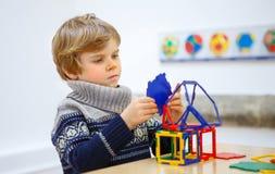 Małe dziecko chłopiec buduje geometryczne postacie z plastikowymi blokami Zdjęcia Royalty Free