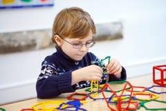 Małe dziecko chłopiec buduje geometryczne postacie z plastikowymi blokami Fotografia Stock
