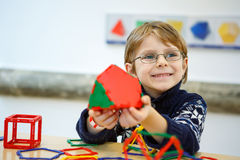 Małe dziecko chłopiec buduje geometryczne postacie z plastikowymi blokami Zdjęcie Royalty Free