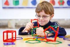 Małe dziecko chłopiec buduje geometryczne postacie z plastikowymi blokami Obrazy Stock