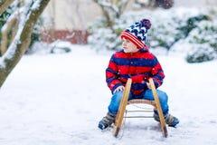 Małe dziecko chłopiec cieszy się sanie przejażdżkę w zimie Obrazy Royalty Free