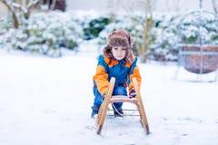 Małe dziecko chłopiec cieszy się sanie przejażdżkę w zimie Zdjęcie Royalty Free