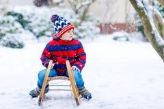 Małe dziecko chłopiec cieszy się sanie przejażdżkę w zimie Zdjęcia Royalty Free