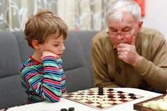 Małe dziecko chłopiec i seniora dziad bawić się wpólnie warcabów gemowych Fotografia Stock