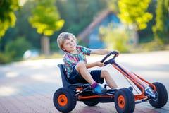 Małe dziecko chłopiec jeżdżenia następu samochód wyścigowy w lecie Zdjęcie Stock