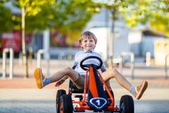 Małe dziecko chłopiec jeżdżenia następu samochód wyścigowy w lecie Obraz Royalty Free