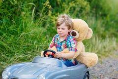 Małe dziecko chłopiec jedzie dużego zabawkarskiego samochód z niedźwiedziem, outdoors zdjęcie royalty free