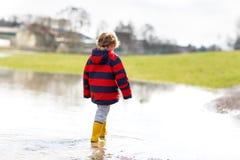 Małe dziecko chłopiec jest ubranym w kałużę na ciepłym pogodnym wiosna dniu, doskakiwanie i Szczęśliwy dziecko wewnątrz obrazy royalty free