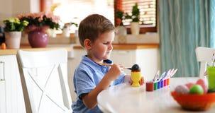 Małe dziecko chłopiec kolorystyki jajka dla Wielkanocnego wakacje w domowej kuchni zdjęcie royalty free