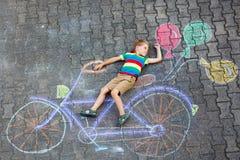 Małe dziecko chłopiec ma zabawę z bicyklem pisze kredą obrazek na ziemi zdjęcie stock