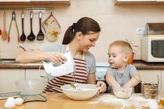 Małe dziecko chłopiec pomocy matka gotować imbirowego ciastko Szczęśliwa rodzinna mama i dziecko w weekendowym ranku w domu związ obraz stock