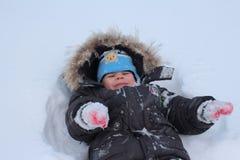 Małe dziecko chłopiec spacery w zimie w śniegu w jardzie radują się w śniegu obraz royalty free