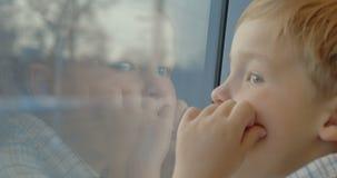 Małe dziecko cieszy się widok od taborowego okno zbiory