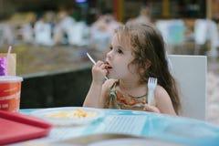 Małe dziecko dziewczyna ma zabawę w restauraci lub kawiarni Obrazy Royalty Free