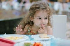 Małe dziecko dziewczyna ma zabawę z jedzeniem przy restauracją lub kawiarnią Fotografia Stock