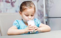 Małe dziecko dziewczyna pije mleko fotografia royalty free