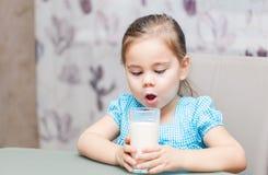 Małe dziecko dziewczyna pije mleko obraz royalty free
